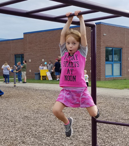 Little girl playing on the monkey bars