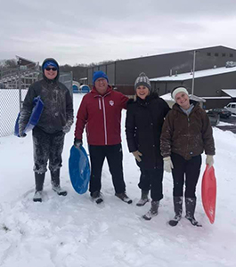 Teachers standing with sleds in snow