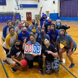 Teachers holding score board after basketball game