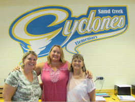 Three staff members standing in front of Cyclones sign
