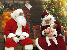 A baby poses with Santa and Mrs. Claus