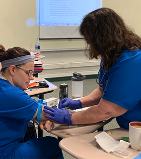 Two medical assisting course students participate in a blood drawing activity
