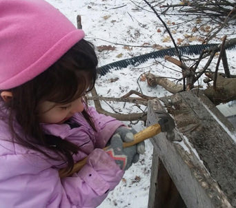Student using hammer to build a beaver lodge