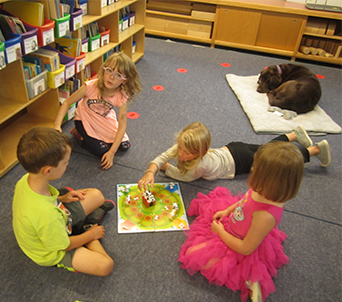 Four students play a game in a library and a dog sleeps nearby