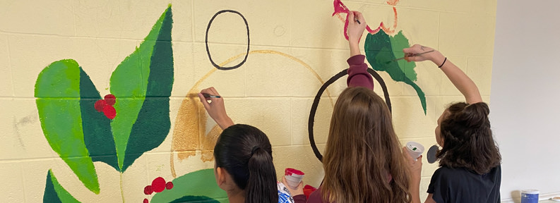 Three students painting a wall mural