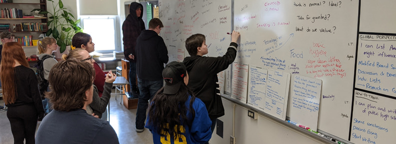 Students writing on a whiteboard