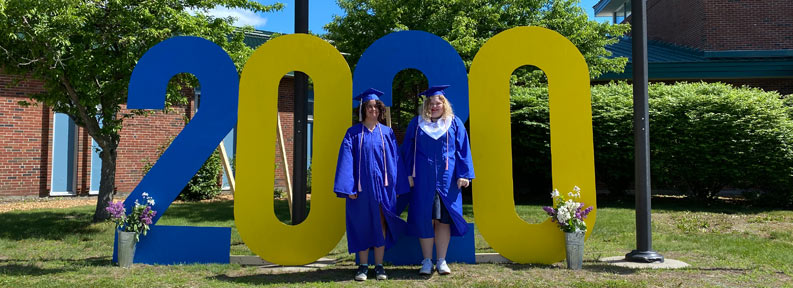 Two graduates standing in front of a 2020 sign