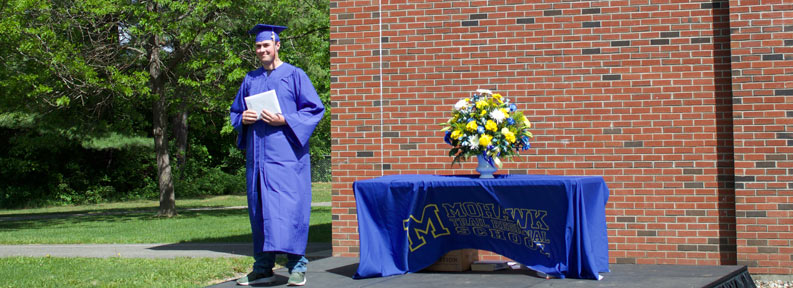 Graduate standing with his diploma