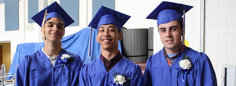 Three happy high school graduates wearing blue cap and gown