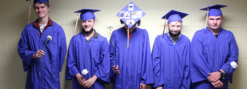 Group of five happy students in cap and gown during graduation