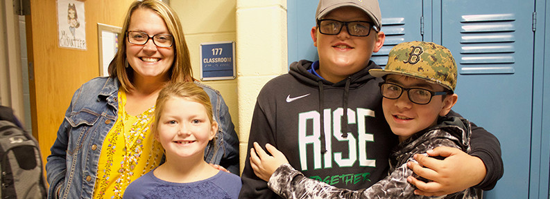 Students and adult smiling in hallway