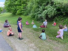students sitting in a circle on grass