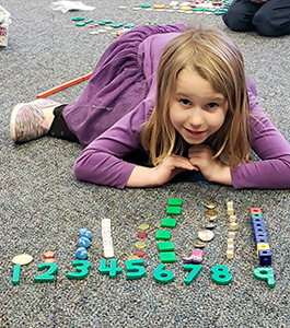 Girl working on counting items from 1 to 9
