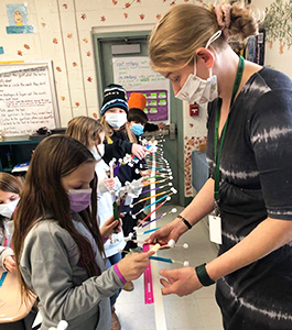 Three students in beekeeper outfits
