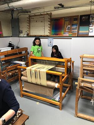 Students at a loom