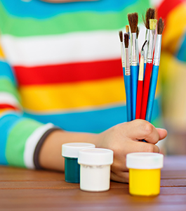Kindergarten student getting ready to paint with colorful colors