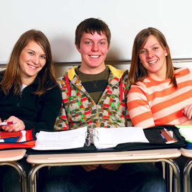 three high school students with binders open at desks