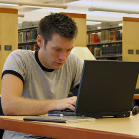 young man at a laptop in a library
