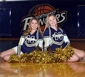 Two cheerleaders posing with pom poms together as they sit on the gym floor in front of a Northwest Rangers sign