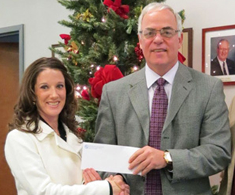 Superintendent receiving a donation from a man in a grey suit