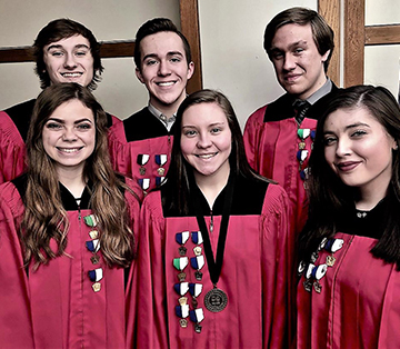 students in red graduation robes