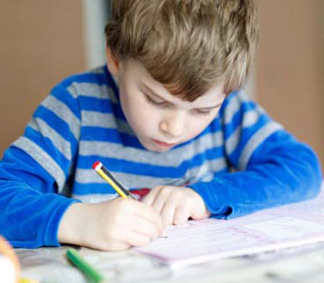 boy in blue shirt writing