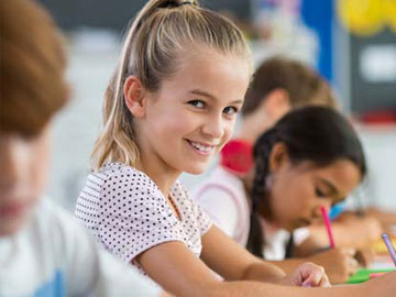 girl smiling at the camera in a row of students
