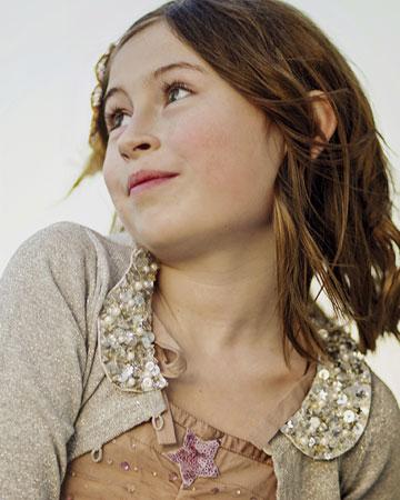 girl wearing brown looking up