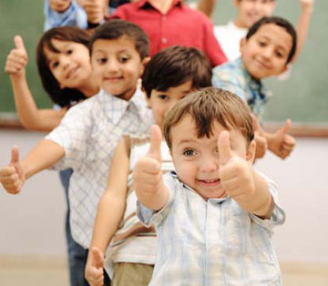 kids in a classroom giving thumbs up