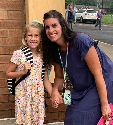 boy with backpack holding apple