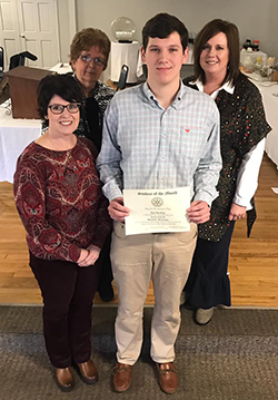 Reid Rushing poses with adults as he holds his certificate