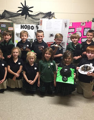 Students gathered with their projects on spiders