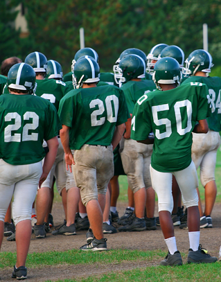 Football players stand outside
