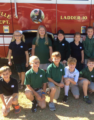 Students stand in front of a fire engine