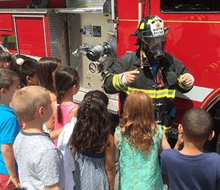 students with a firefighter