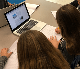 students doing school work on a laptop