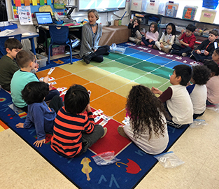 Students and their teacher sitting on a colorful rug