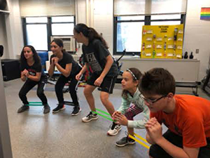 Students bend down as part of an exercise together