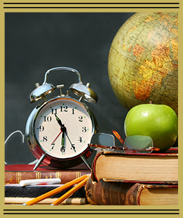 a clock, apple and globe all sitting on a stack of books
