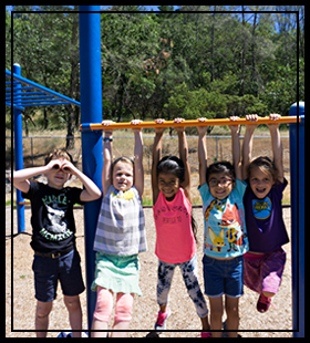 5 students hanging from the monkey bars