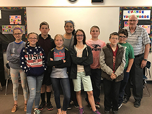 Academic team stands smiling in a classroom