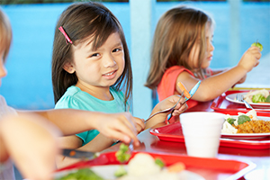 Smiling girl sits with lunch tray