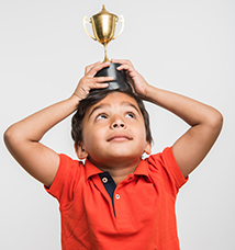 Child holds a winning trophy over his head
