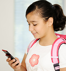 Smiling girl with backpack looks at cell phone