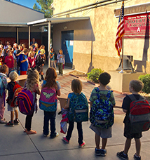 Students and teachers recite the pledge of allegiance in front of an American flag outside