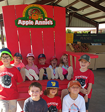 Children sitting on and in front of a big red chair at Apple Annies