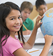 Student in class pointing at globe
