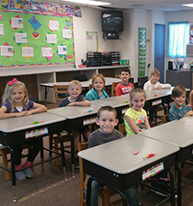 Two rows of smiling students sit behind their desks