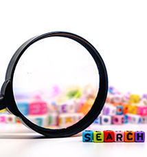 Magnifying glass sits next to colorful blocks spelling out the word search