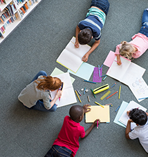 Children lying on the floor and drawing